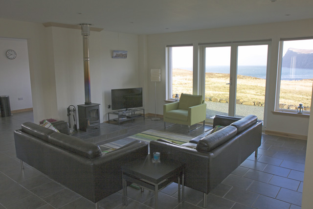 Open plan lounge with sea views and woodburning stove